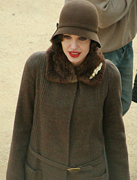 From waist–up, a pale skinned, red-lipped slender woman in a cloche hat and fastened fur-trimmed coat, both brown