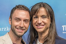 Måns Zelmerlöv standing next to Petra Mede at a press conference at the Eurovision Song Contest 2016