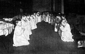 Two rows of little boys, about 20 in total, kneel before their beds in the dormitory of a residential nursery. Their eyes are shut and they are in an attitude of prayer. They wear long white night gowns and behind them are their iron framed beds.