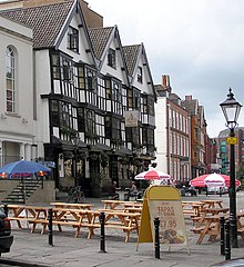 A seventeenth-century timber-framed building with three gables and a traditional inn sign showing a picture of a sailing barge. Some drinkers sit at benches outside on a cobbled street. Other old buildings are further down the street, and in the background part of a modern office building can be seen.