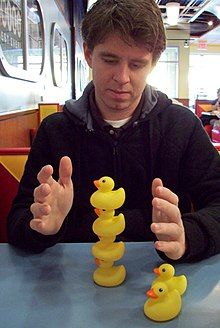 Munroe looking over a stack of rubber ducks on a table