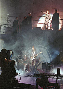 A concert stage in front of a wall with 2 levels. Five men stand on a balcony, including Roger Waters, who is saluting with his arm. On the lower level is a drum kit and a man playing guitar.