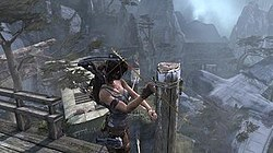 The player character, standing atop a high ledge, creating a makeshift zipline to a lower ledge by shooting an arrow.