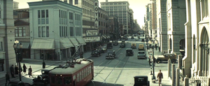 Elevated daytime view of a busy city crossroads, looking down one street along which a series of tall buildings recede into the distance. Pedestrians line the sidewalks, cars litter the streets; a bright red electric streetcar features in the foreground