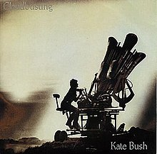 cover of Kate Bush's single, showing her sitting astride a reproduction of a 'cloudbuster'