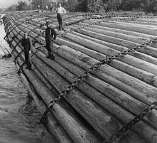Three men in work clothes stand on an enormous raft of logs held together with cable chains. In the background, another three men work on a distant part of the raft, only part of which is visible. The pile of logs appears to be taller than any of the men.