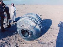 Cylindrical rocket fragment on sand, with men looking at it