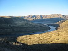 A relatively small river winds through a series of sparsely vegetated brown hills under a nearly cloudless blue sky. The river and the low hills are in shade, while the hilltops and a large hillside in the foreground are sunlit.